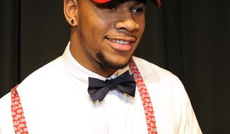 Grayson High School football player Robert Nkemdiche, the nation's top recruit, announces his intent to play college football for Ole Miss during a signing day ceremony at his high school auditorium in Grayson, Ga., Wednesday Feb. 6, 2013. (AP Photo/David Tulis)