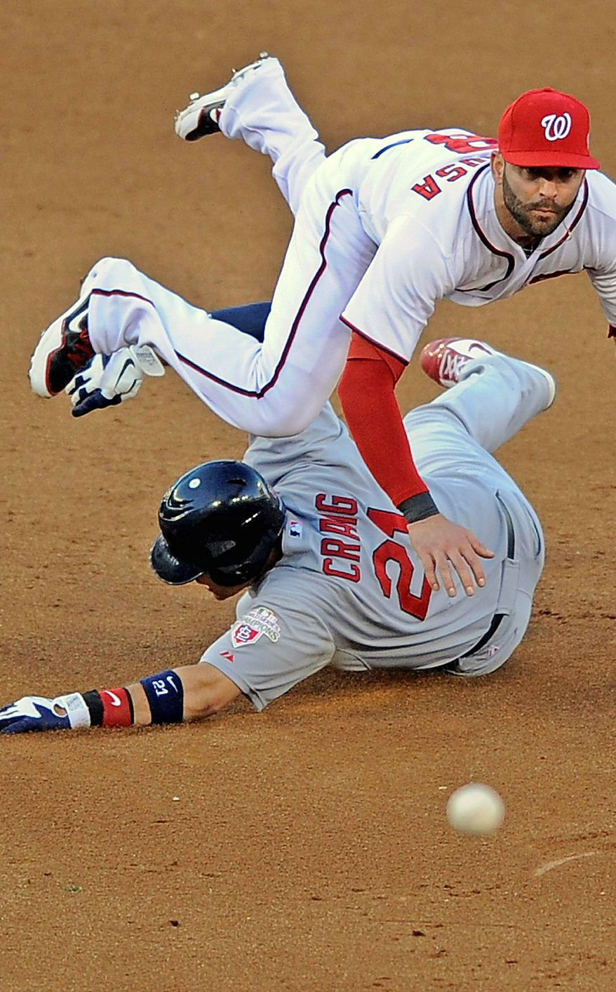 Washington Nationals second baseman Danny Espinosa, top, leaps over St. Louis Cardinals' Allen Craig as he throws out Cardinals batter Yadier Molina at first base in the sixth inning of Game 4 of the National League division baseball series on Thursday, Oct. 11, 2012, in Washington. Craig was safe at second base. (AP Photo/Nick Wass)