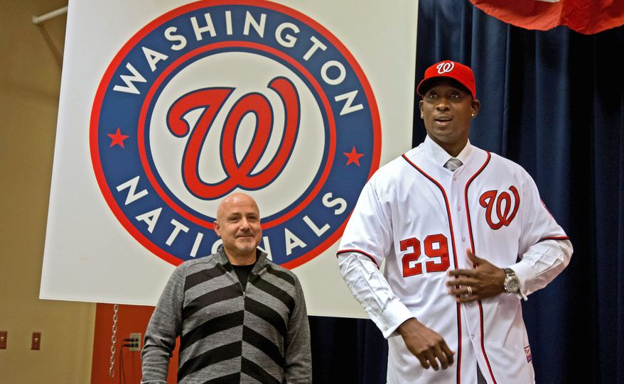 Washington Nationals general manager Mike Rizzo (left) looks on as newly-acquired pitcher Rafael Soriano models his jersey Jan. 17, 2013, during an introductory news conference at Nationals Park in Washington. Rizzo also discussed the three-team trade that sent Michael Morse to the Seattle Mariners in exchange for pitching prospect A.J. Cole from the Oakland Athletics. (Associated Press)