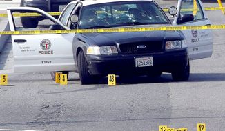 A bullet-damaged Los Angeles police vehicle with crime scene tape around it sits on a street in Corona, Calif. Christopher Jordan Dorner is being sought after three killings. (Associated Press)