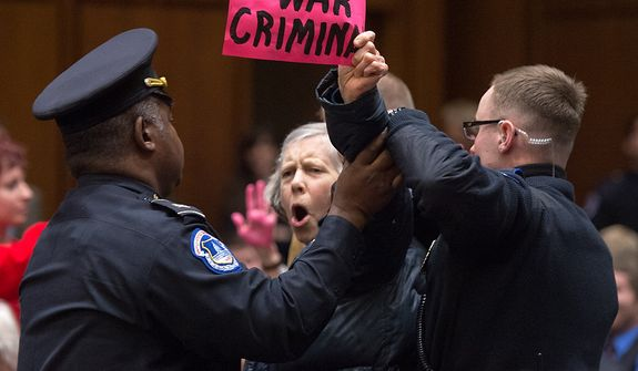 An anti-war protester is removed as John O. Brennan arrives to testify before the Senate Select Committee on Intelligence at a hearing on Capitol Hill in Washington on Thursday, Feb. 7, 2013, on his nomination to head the Central Intelligence Agency. (Andrew Harnik/The Washington Times)