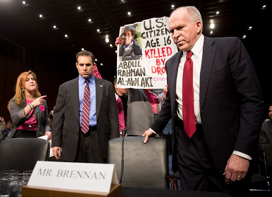 Anti-war protesters yell and hold signs as John O. Brennan arrives to testify before the Senate Select Committee on Intelligence at a hearing on Capitol Hill in Washington on Thursday, Feb. 7, 2013, on his nomination to head the Central Intelligence Agency. (Andrew Harnik/The Washington Times)