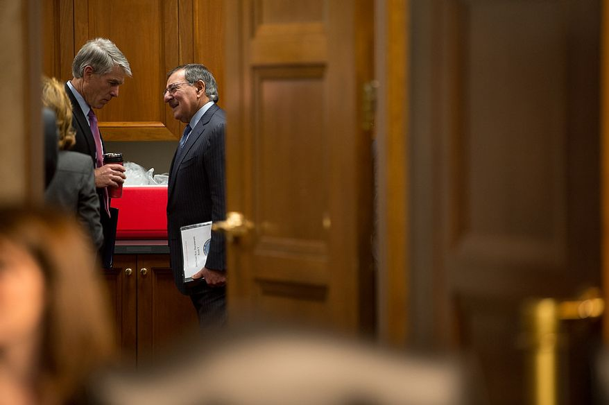 ** FILE ** Sen. Mark Udall (left), Colorado Democrat, talks with Secretary of Defense Leon E. Panetta before Mr. Panetta testifies before the Senate Armed Services Committee on Capitol Hill in Washington on Thursday, Feb. 7, 2013, on the Defense Department's response to the attack on U.S. facilities in Benghazi, Libya. (Andrew Harnik/The Washington Times)