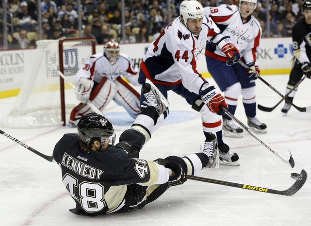 Pittsburgh Penguins' Tyler Kennedy (48) controls the puck from a seated position as Washington Capitals' Roman Hamrlik (44) defends in the second period of an NHL hockey game Thursday, Feb. 7, 2013, in Pittsburgh. (AP Photo/Keith Srakocic)