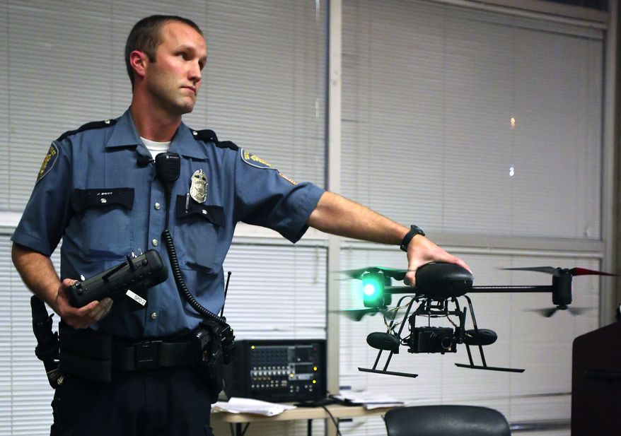 ** FILE ** Seattle police Officer Jim Britt demonstrates an unmanned aerial vehicle during an informational meeting at which the police attempted answer questions about their drone program at the Garfield Community Center in Seattle on Thursday, Oct. 25, 2012. The mayor of Seattle ended the police department's drone program in February after residents protested. (AP Photo/The Seattle Times, Colin Diltz)