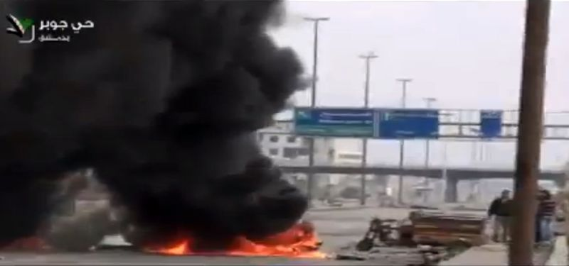 This image taken from video obtained from Ugarit News on Friday, Feb. 8, 2013, which has been authenticated based on its contents and other AP reporting, show smoke and fire rising on a main highway in Damascus, Syria. Rebels pushed forward in their