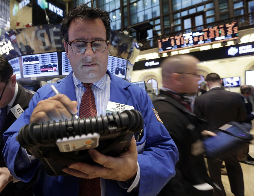 Trader Peter Costa (left) works on the floor of the New York Stock Exchange on Feb. 8, 2013. (Associated Press)