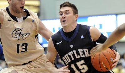 Butler guard Rotnei Clarke (15) drives to the basket against George Washington's Patricio Garino (13) and Kethan Savage (11) during the first half of an NCAA college basketball game, Saturday, Feb. 9, 2013, in Washington. (AP Photo/Nick Wass)