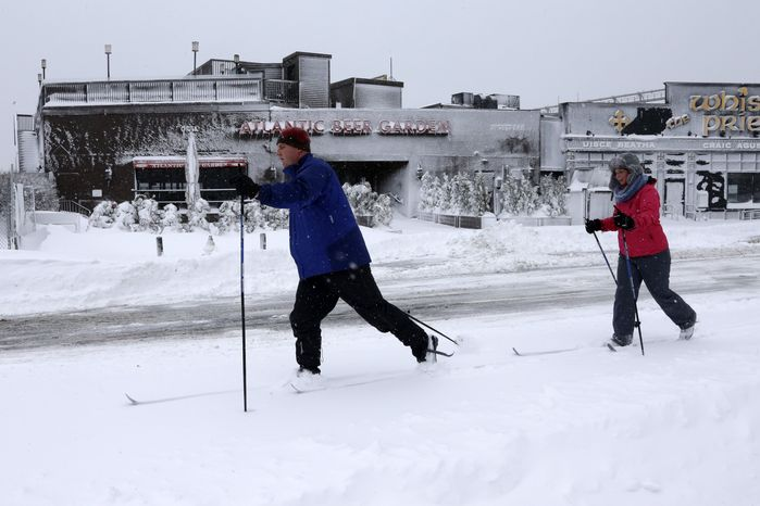 Brendan, left, and Lisa Koeniger, of Boston, cross country ski through the Seaport area of Boston, Saturday, Feb. 9, 2013. A behemoth storm packing hurricane-force wind gusts and blizzard conditions swept through the Northeast on Saturday, dumping more than 2 feet of snow on New England and knocking out power to 650,000 homes and businesses.(AP Photo/Gene J. Puskar)