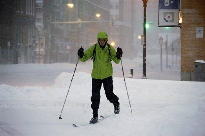 A pedestrian uses skis to travel through the deserted snow-covered streets of Boston early Saturday, Feb. 9, 2013. (Associated Press)