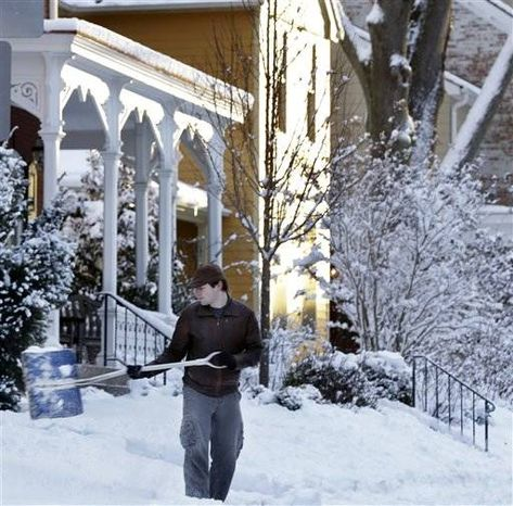 As the early morning sun reflects on homes, Eric Weir shovels snow Saturday, Feb. 9, near Newtown, Pa. A behemoth storm packing hurricane-force wind gusts and blizzard