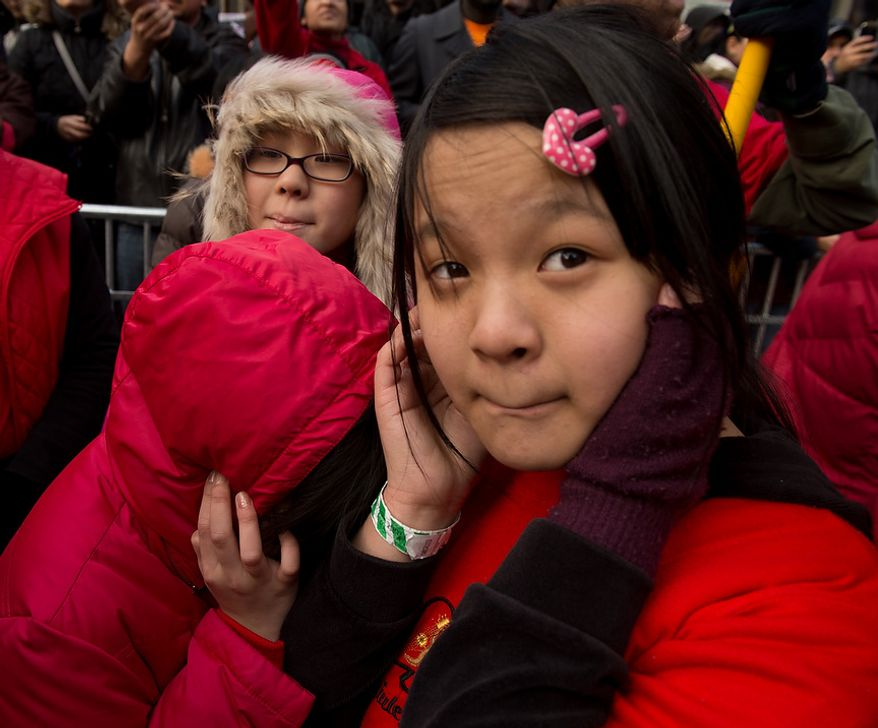 Girls plug their ears from loud firecrackers as Washington, D.C. celebrates the Chinese New Year with a parade down H Street in Chinatown for the year of the snake, Washington, D.C., Sunday, February 10, 2013. (Andrew Harnik/The Washington Times)