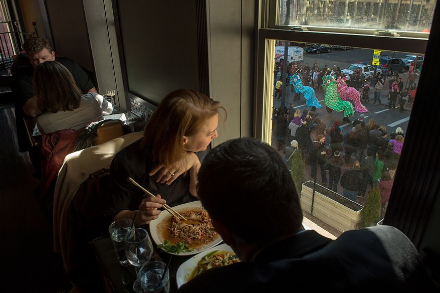 A couple looks out the window of a restaurant and watches as Washington, D.C. celebrates the Chinese New Year with a parade down H Street in Chinatown for the year of the snake, Washington, D.C., Sunday, February 10, 2013. (Andrew Harnik/The Washington Times)
