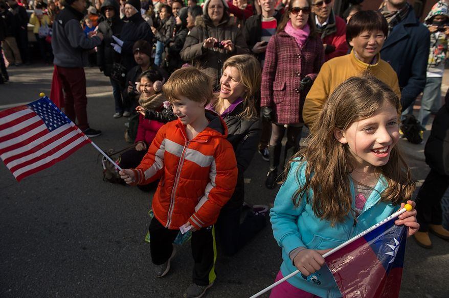 Ben, 5, and Rachel, 8, Chapin of Arlington, Va., wave flags as they watch a parade down H Street in Chinatown for the Chinese New Year which is the year of the snake, Washington, D.C., Sunday, February 10, 2013. (Andrew Harnik/The Washington Times)