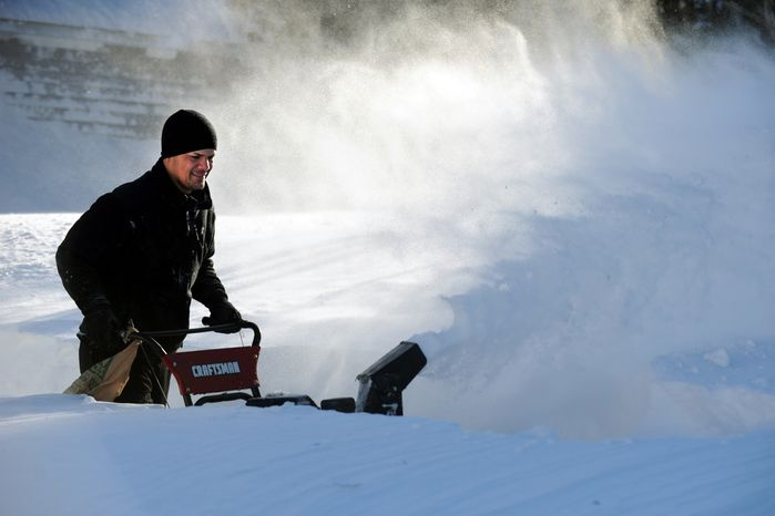 Tony Colon uses a snow blower to clear his driveway in Derby, Conn., as residents face massive snow removal on Saturday, Feb. 9, 2013, following a severe blizzard that dumped up to 3 feet of snow across the state. (AP Photo/The Connecticut Post, Autumn Driscoll)