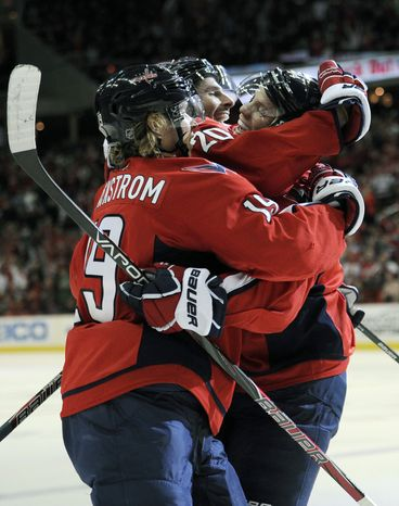 Washington Capitals defenseman John Carlson, right, celebrates a goal scored by teammate Troy Brouwer (20) and Nicklas Backstrom (19), of Sweden, during the first period of an NHL hockey game against the Florida Panthers, Saturday, Feb. 9, 2013, in Washington. (AP Photo/Nick Wass)