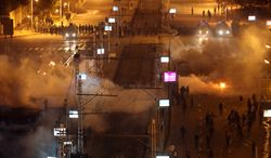 ** FILE ** Egyptian security police fire tear gas at protesters during clashes next to the presidential palace in Cairo, Egypt, Friday, Feb. 8, 2013. Egypt has witnessed a fresh cycle of violence over the past two weeks since the second anniversary of the 2011 uprising that deposed longtime autocrat Hosni Mubarak, with clashes across the country having left scores dead and hundreds injured. (AP Photo/Khalil Hamra)