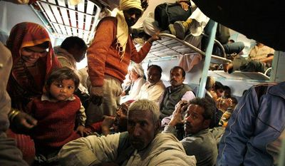 Hindu devotees returning from the Maha Kumbh pilgrimage travel in an overcrowded train coach from the main railroad station of Allahabad, India, on Monday, Feb. 11, 2013. (AP Photo/Rajesh Kumar Singh)