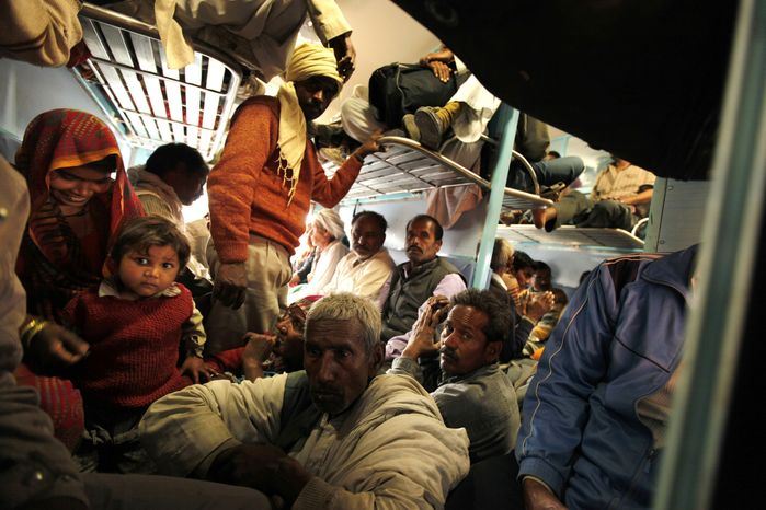 Hindu devotees returning from the Maha Kumbh pilgrimage travel in an overcrowded train coach from the main railroad station of Allahabad, India, on Monday, Feb. 11, 2013