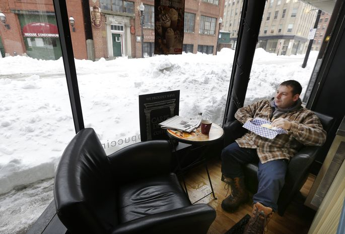 Matt Church enjoys his breakfast at a coffee shop in downtown Haverhill, Mass., on Monday, Feb. 11, 2013. Beleaguered Massachusetts residents returned to work on Monday for the first time since the weekend blizzard, crawling along narrow snow-covered secondary roads and being greeted by a new wintry mix of sleet and freezing rain. (AP Photo/Elise Amendola)