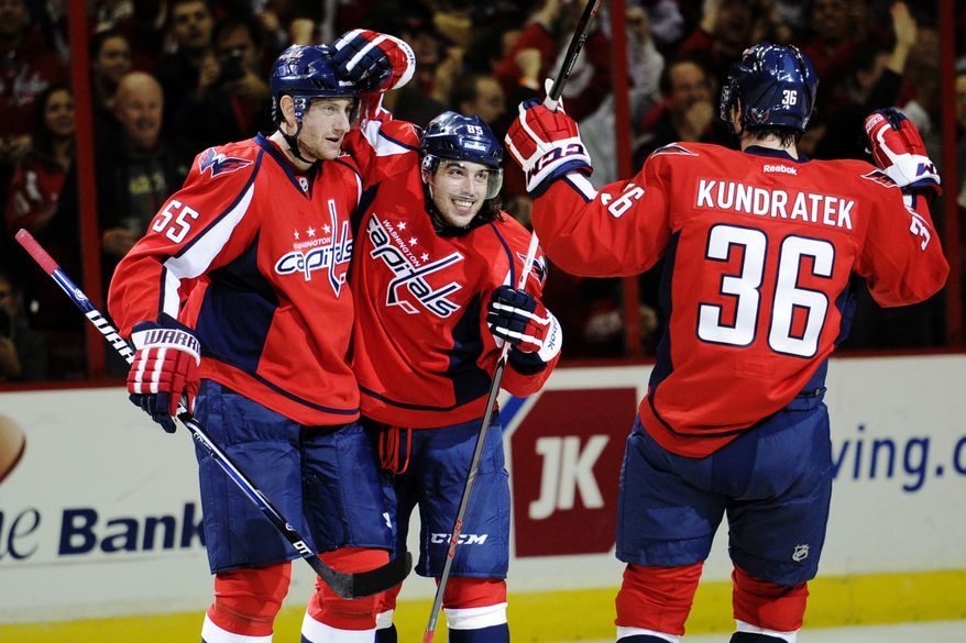 Washington Capitals center Mathieu Perreault (85) celebrates his goal with Jeff Schultz (55) and Tomas Kundratek (36), of the Czech Republic, during the third period of an NHL hockey game against the Florida Panthers, Saturday, Feb. 9, 2013, in Washington. The Capitals won 5-0. (AP Photo/Nick Wass)