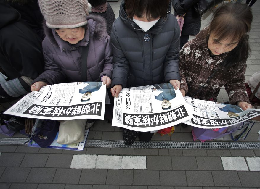 ** FILE ** Women in Tokyo read copies of an extra edition of a Japanese newspaper reporting North Korea's nuclear test on Tuesday, Feb. 12, 2013. (AP Photo/Itsuo Inouye)