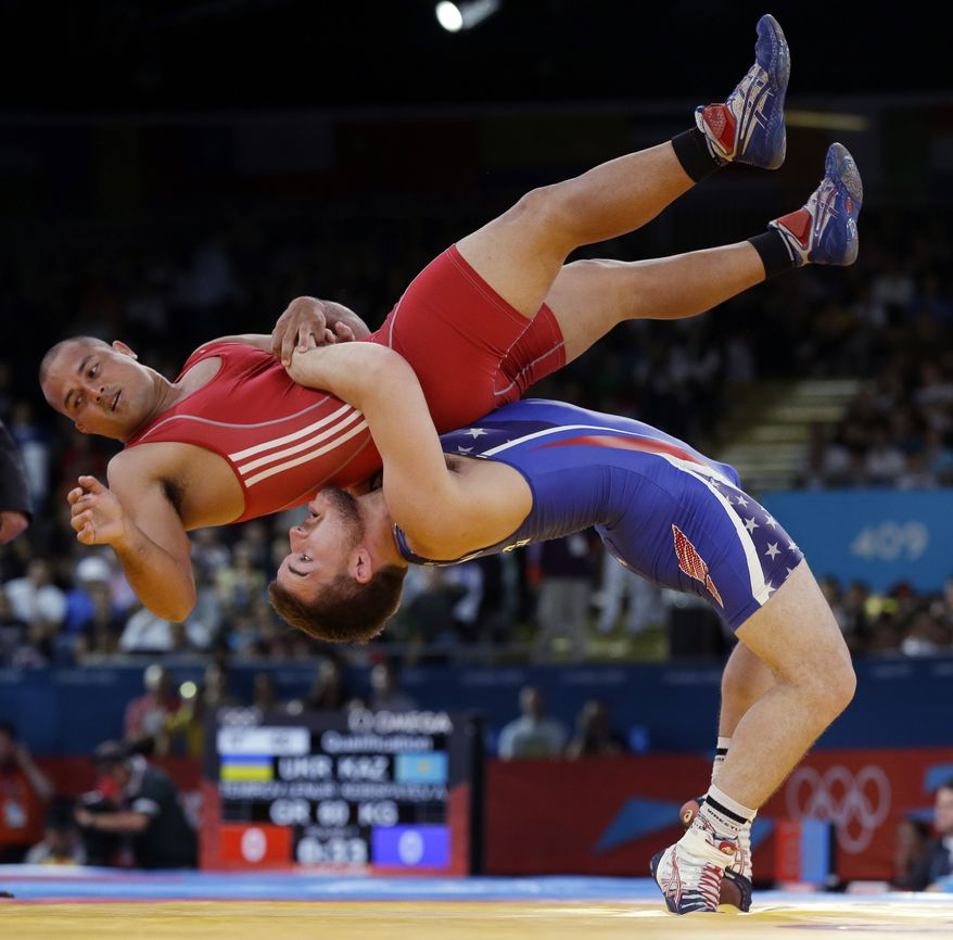 **FILE** In this Monday, Aug. 6, 2012 file photo Keitani Graham of Micronesia competes against Charles Edward Betts of the United States, right, during the 84-kg Greco-Roman wrestling competition at the 2012 Summer Olympics, in London. An official familiar with the decision says IOC leaders have dropped wrestling from the program for the 2020 Olympics. In a surprise decision Tuesday Feb. 12, 2013, the official tells The Associated Press that the IOC executive board decided to retain modern pentathlon and remove wrestling instead. (AP Photo/Paul Sancya, File)