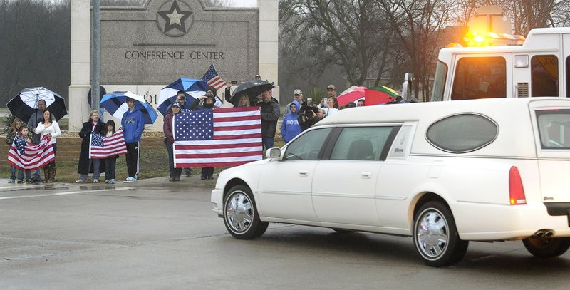 Mourners hold U.S. flags as a hearse containing Chris Kyle's casket leads a motorcade leaving the Multi-Purpose Stadium, in Midlothian, Texas, Tuesday, Feb. 12, 2013, for the 200-mile journey to Austin, where Kyle will be buried at the Texas State Cemetery. (AP Photo/Star-Telegram, Max Faulkner)