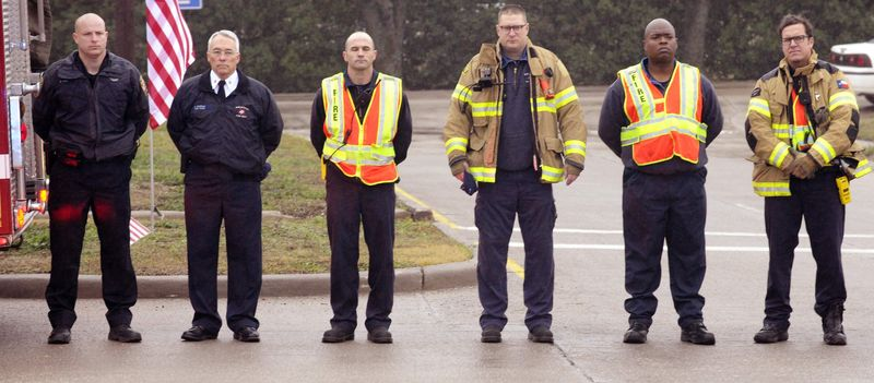 Members of Midlothian Fire Department pay their respects during a procession for Chris Kyle in Midlothian, Texas, Tuesday, Feb. 12, 2013, for the 200-mile journey to Austin, where Kyle will be buried at the Texas State Cemetery. Some 7,000 people attended a two-hour memorial service for Kyle at Cowboys Stadium in Arlington on Monday. Kyle and his friend Chad Littlefield were shot and killed Feb 2. at a North Texas gun range. (AP Photo/Star-Telegram, Max Faulkner)