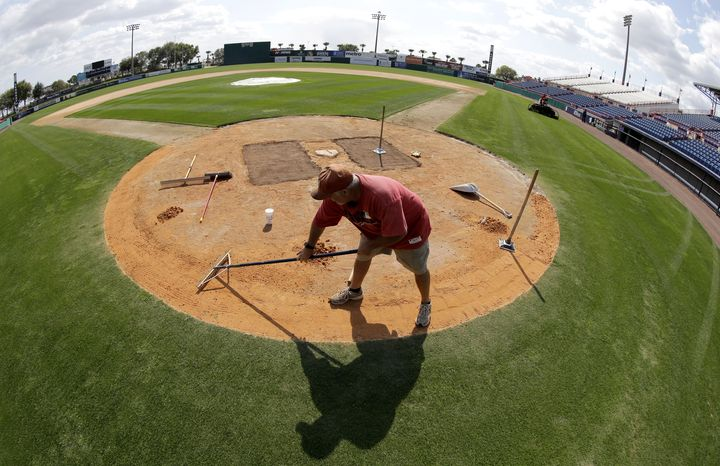 Grounds crew member Michael Schnee works around home plate at Space Coast Stadium, the Washington Nationals spring training facility, Monday, Feb. 11, 2013 in Viera, Fla. Nationals pitchers and catchers first spring training workout is Thursday. (AP Photo/David J. Phillip)