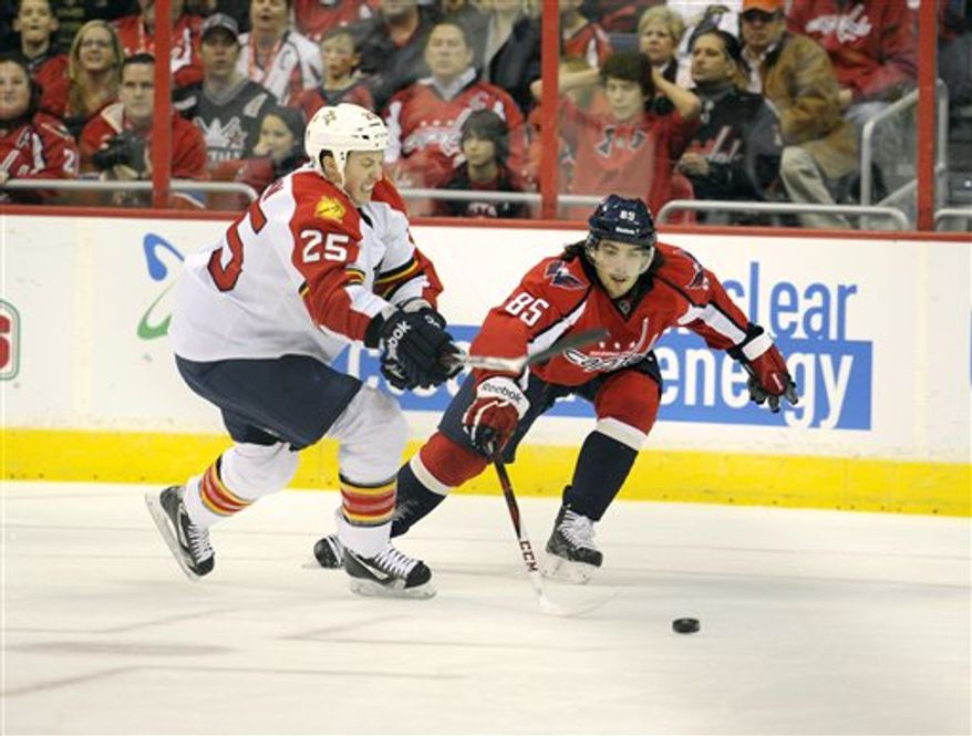 Washington Capitals center Mathieu Perreault (85) battles for the puck against Florida Panthers center Jerred Smithson (25) during the third period of an NHL hockey game, Saturday, Feb. 9, 2013, in Washington. The Capitals won 5-0. (AP Photo/Nick Wass)