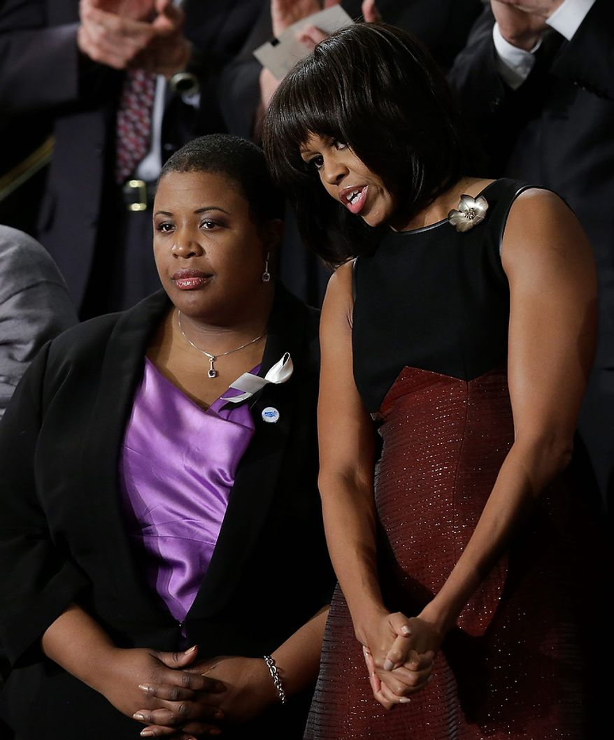 First lady Michelle Obama stands with Cleopatra Cowley-Pendelton before President Barack Obama's State of the Union address during a joint session of Congress on Capitol Hill in Washington, Tuesday Feb. 12, 2013. (AP Photo/Pablo Martinez Monsivais)