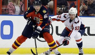 Florida Panthers center Tomas Kopecky (82) and Washington Capitals defenseman Mike Green (52) battle for the puck during the first period of an NHL hockey game on Tuesday, Feb. 12, 2013, in Sunrise, Fla. (AP Photo/Wilfredo Lee)