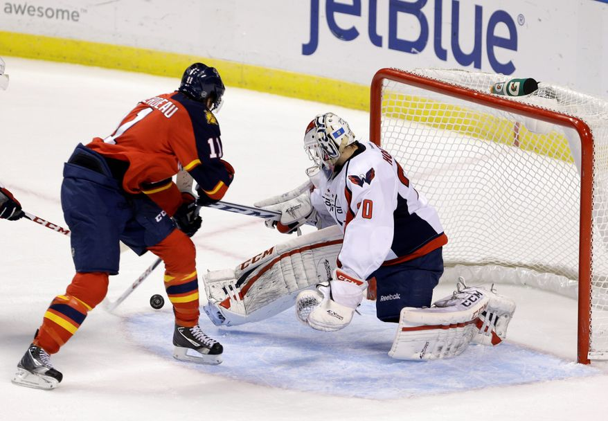 Florida Panthers center Jonathan Huberdeau (left) scores against Washington Capitals goalie Braden Holtby during the second period of an NHL hockey game on Tuesday, Feb. 12, 2013, in Sunrise, Fla. (AP Photo/Wilfredo Lee)