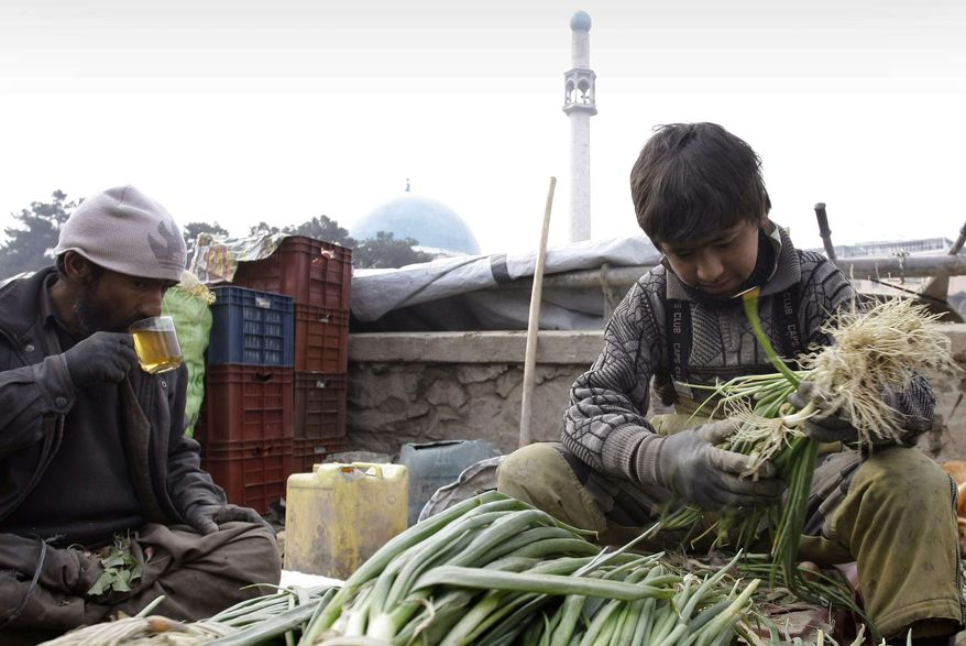 An Afghan vendor, right, sorts out vegetables as his father drinks tea in Kabul, Afghanistan, on Wednesday, Feb. 13, 2013. (AP Photo/Musadeq Sadeq)
