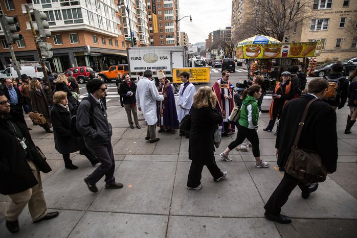 Sidewalk traffic speeds by Bishop Mariann Edgar Budde of the Washington Episcopal Diocese and Father Nathan Humphrey as they place ash on the foreheads of morning commuters to celebrate Ash Wednesday, a Catholic tradition, next to t