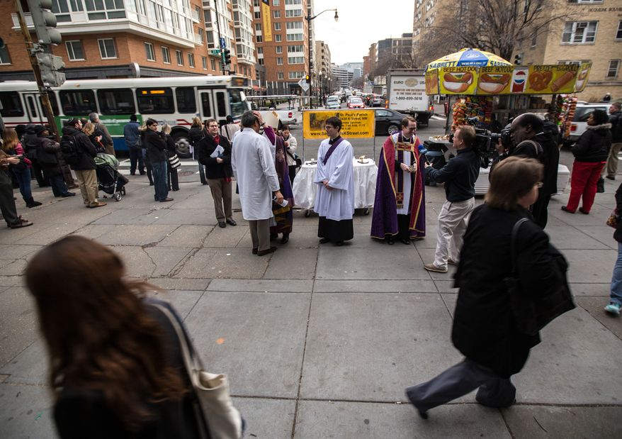 Sidewalk traffic speeds by Bishop Mariann Edgar Budde of the Washington Episcopal Diocese and Father Nathan Humphrey as they place ash on the foreheads of morning commuters to celebrate Ash Wednesday, a Catholic tradition, next to the Foggy Bottom-GWU Metro station in D.C. on Feb. 13, 2013. (Andrew S. Geraci/The Washington Times)