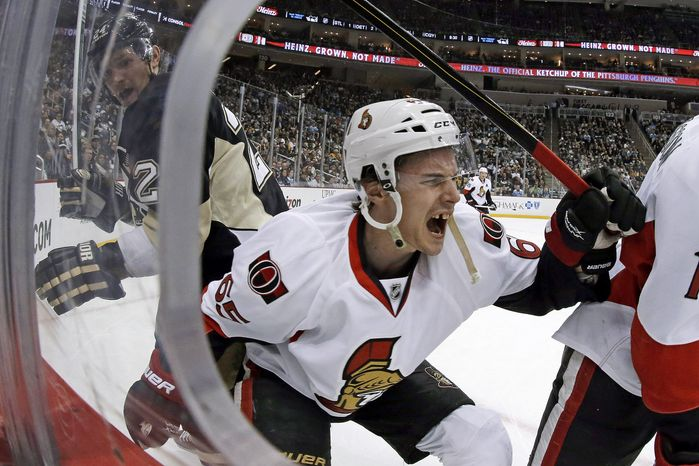 Ottawa Senators defenseman Erik Karlsson (65) grimaces as he falls to the ice after colliding with Pittsburgh Penguins left wing Matt Cooke, left, during the second period of an NHL hockey game in Pittsburgh Wednesday, Feb. 13, 2013. Karlsson was helped off the ice. (AP Photo/Gene J. Puskar)