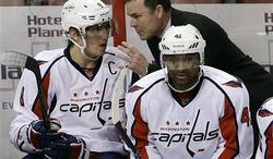 Washington Capitals head coach Adam Oates (center) talks to captain Alex Ovechkin (left) as right wing Joel Ward (right) looks on during the second period of an NHL hockey game against the Florida Panthers on Tuesday, Feb. 12, 2013, in Sunrise, Fla. (AP Photo/Wilfredo Lee)
