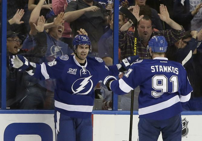 Fans of the Tampa Bay Lightning cheer as Lighting right wing Teddy Purcell (left) celebrates with fellow player Steven Stamkos (91) after scoring against the Philadelphia Flyers during the first period of an NHL hockey game on Sunday, Jan. 27, 2013, in Tampa, Fla. (AP Photo/Chris O'Meara)