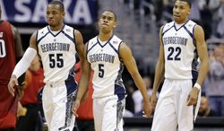 **FILE** In this Jan. 26, 2013, file photo, Georgetown guard Jabril Trawick (55), guard Markel Starks (5) and forward Otto Porter Jr. (22) walk to the bench during a timeout during the second half of an NCAA college basketball game against Louisville in Washington. Georgetown coach John Thompson III does such a good job selling his team-orientated system that sometimes his best players don't assert themselves the way they should. In recent games, the light bulb has come on for Porter and Starks, and that's why the Hoyas are contending for a Big East title. (AP Photo/Alex Brandon, File)