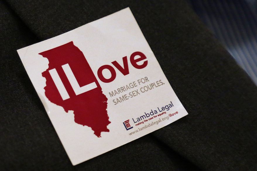 **FILE** A supporter of same sex-marriage wears a sticker on her jacket before attending a state Senate Executive Committee hearing on the topic at the Illinois Capitol in Springfield, Ill., on Jan. 3, 2013. (AP Photo/Seth Perlman)