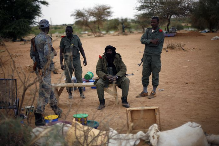 Malian soldiers man a checkpoint at the northern entrance to Gao, Mali, on Wednesday, Feb. 13, 2013. French soldiers on Wednesday recovered an enormous stash of explosives that authorities believe radical Islamic fighters were using to make bo