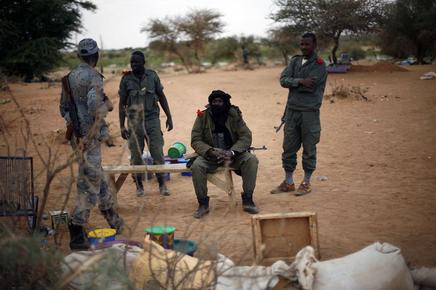 Malian soldiers man a checkpoint at the northern entrance to Gao, Mali, on Wednesday, Feb. 13, 2013. French soldiers on Wednesday recovered an enormous stash of explosives that authorities believe radical Islamic fighters were using to make bombs for attacks on northern Mali's largest city, a Malian military spokesman said. (AP Photo/Jerome Delay)