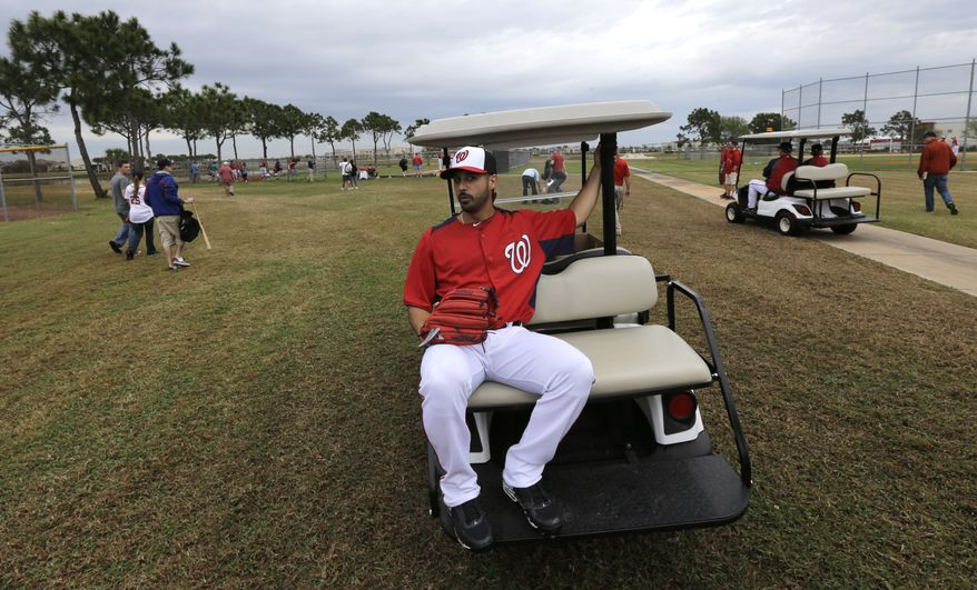 Washington Nationals pitcher Gio Gonzalez rides on the back of a cart during a spring training baseball workout Thursday, Feb. 14, 2013, in Viera, Fla. (AP Photo/David J. Phillip)
