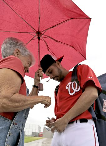 Washington Nationals pitcher Gio Gonzalez, right, signs an autograph for Nena Stevens, of Winter Park, Fla., as rain falls during a spring training baseball workout Thursday, Feb. 14, 2013, in Viera, Fla. (AP Photo/David J. Phillip)