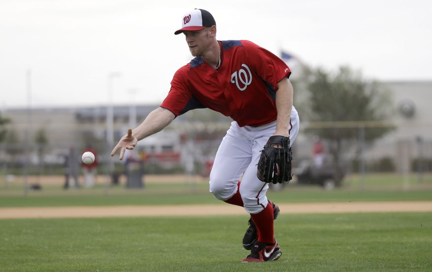 Washington Nationals pitcher Stephen Strasburg tosses the ball to home plate during a spring training baseball workout Thursday, Feb. 14, 2013, in Viera, Fla. (AP Photo/David J. Phillip)