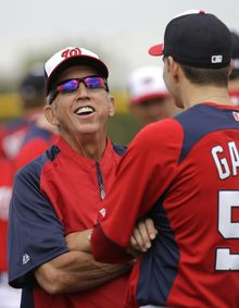 Washington Nationals manager Davey Johnson, left, laughs as he talks with pitcher Christian Garcia during a spring training baseball workout Thursday, Feb. 14, 2013, in Viera, Fla. (AP Photo/David J. Phillip)