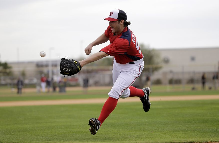 Washington Nationals pitcher Tanner Roark tosses the ball to home plate with his glove as part of a drill during a spring training baseball workout Thursday, Feb. 14, 2013, in Viera, Fla. (AP Photo/David J. Phillip)