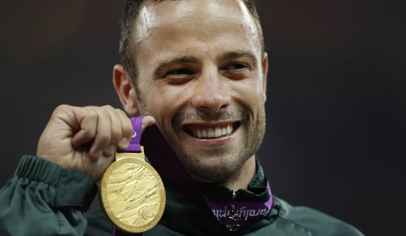**FILE** Gold medalist South Africa's Oscar Pistorius poses Sept. 8, 2012, with his medal during the ceremony after winning the men's 400 meters T44 category final during the athletics competition at the 2012 Paralympics in London. (Associated Press)